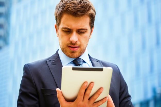 man checking his tablet | The Rules Of Email Etiquette