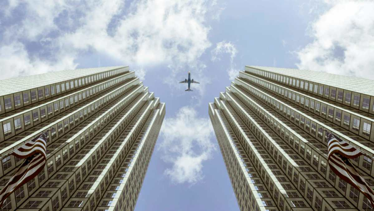 plane between two high rise buildings | Cap Rate: Everything You Need To Know | Cap rate formula